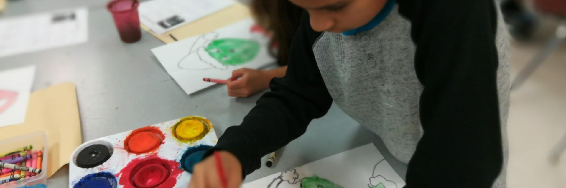 Third graders creating water color Grinches in art class.