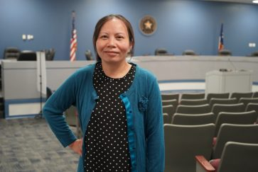Woman posing for picture in the Arlington ISD Boardroom